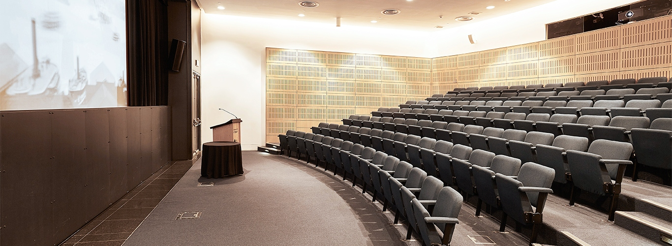 Theatre area with seating, speakers podium and screen.
