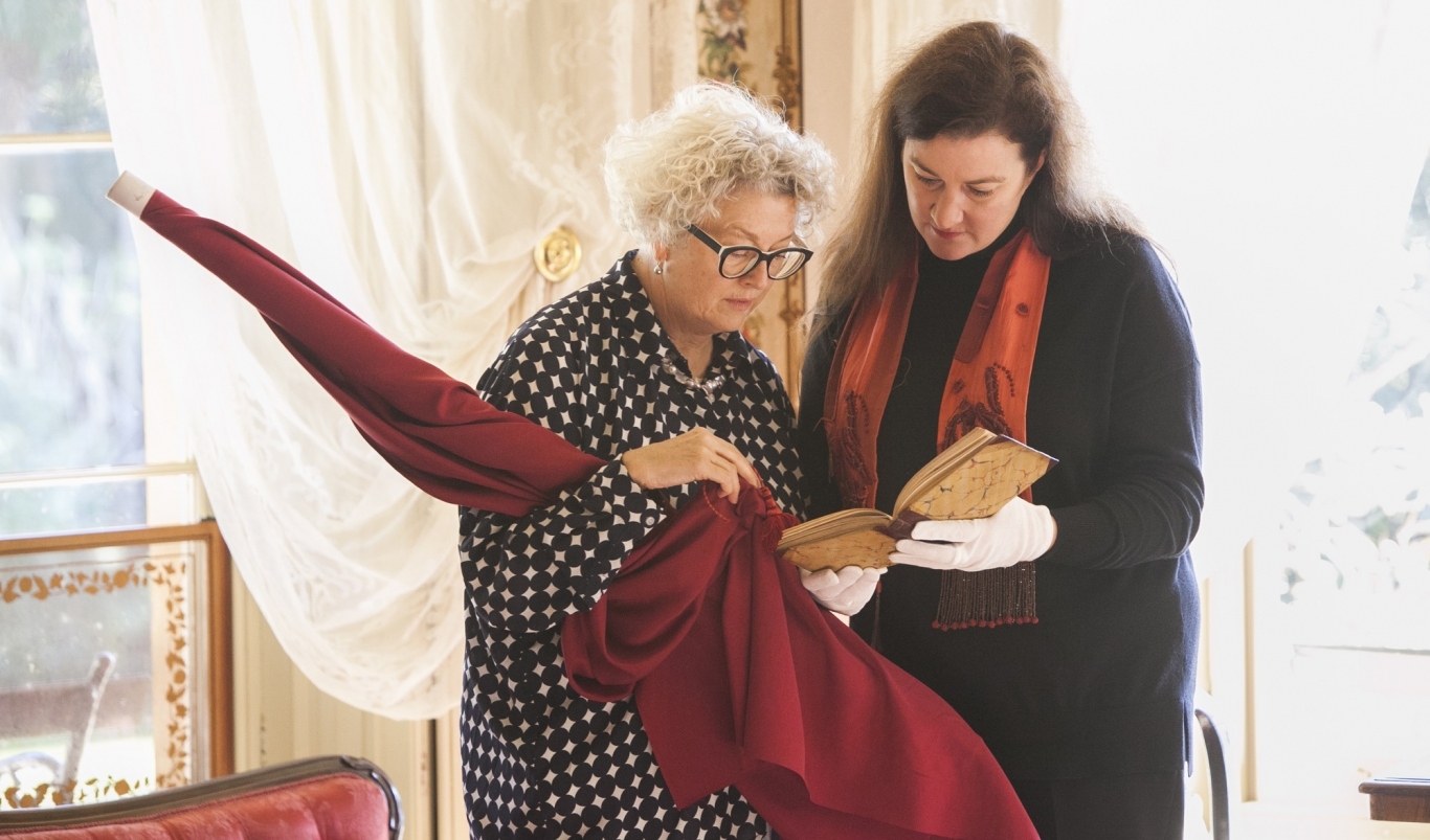 Two women looking at old book, one holding dark red cloth bolt.