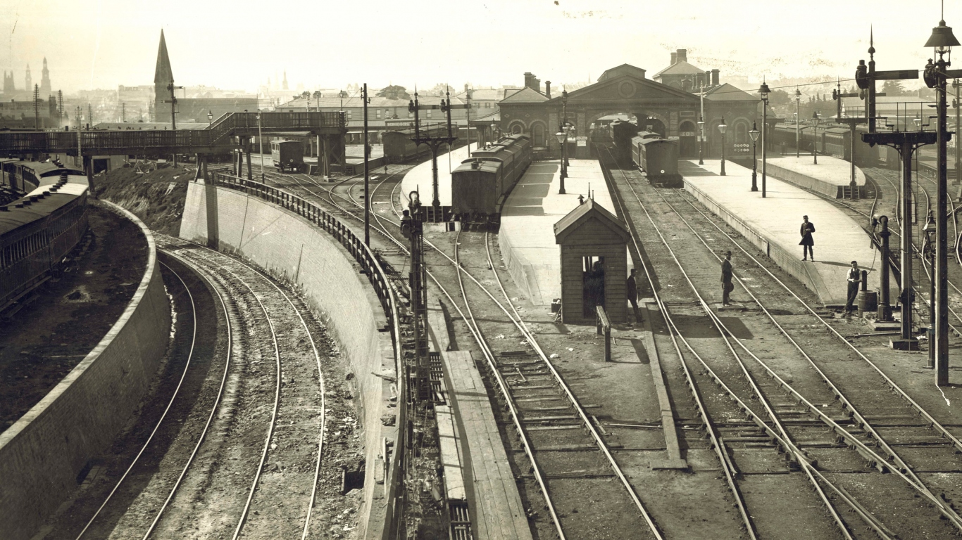Black and white image of train tracks and station.