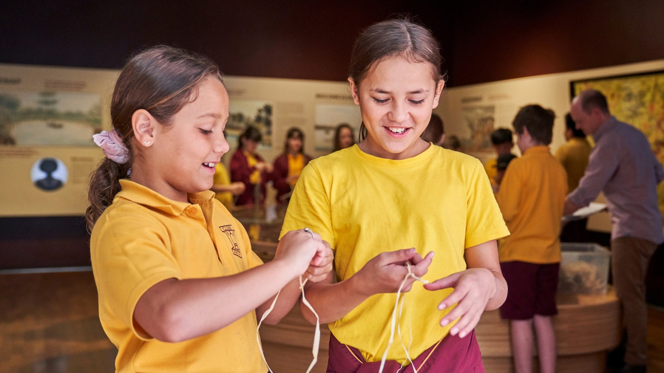 Two girls in school uniform making string in exhibition space with other students behind.
