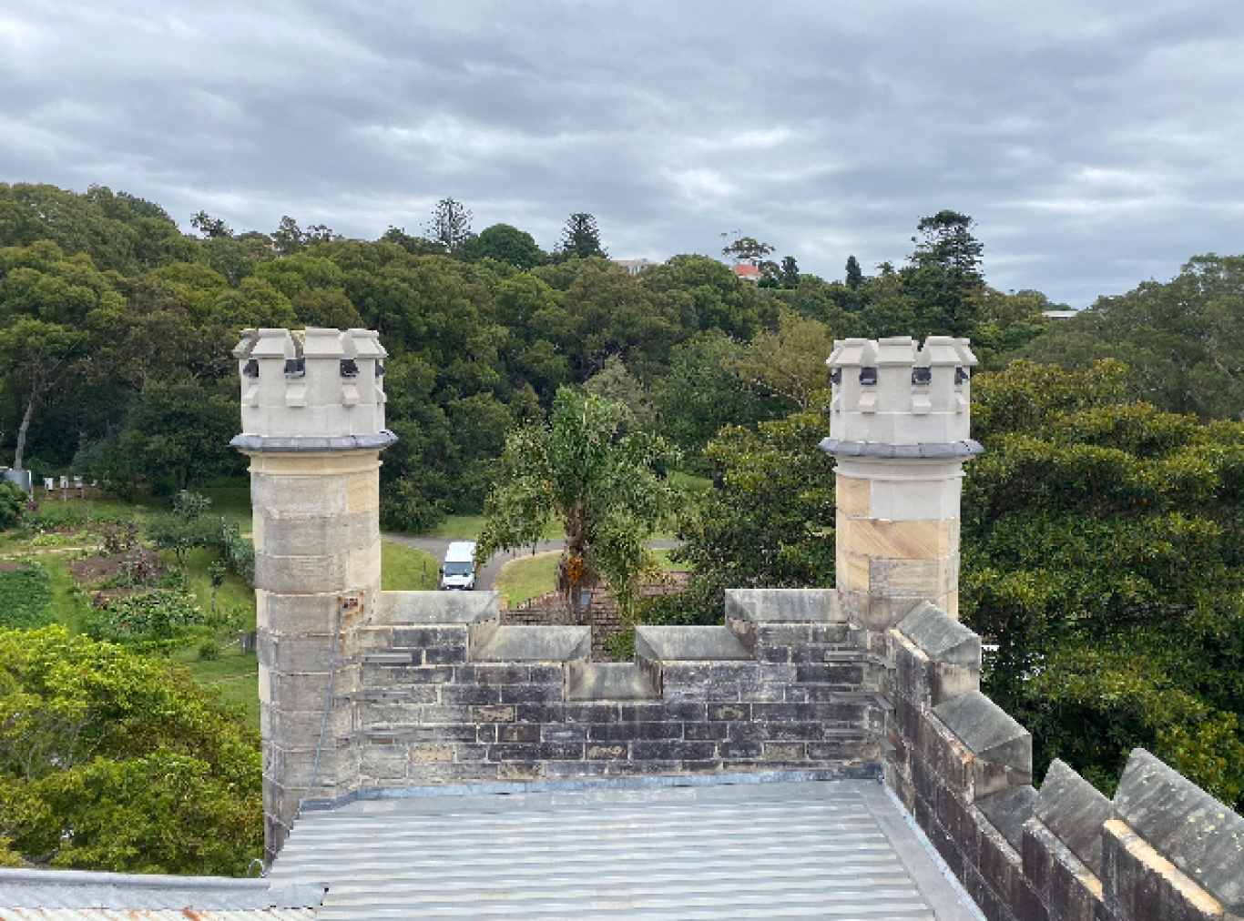 Looking over a pair of sandstone turrets towards treetops and garden.