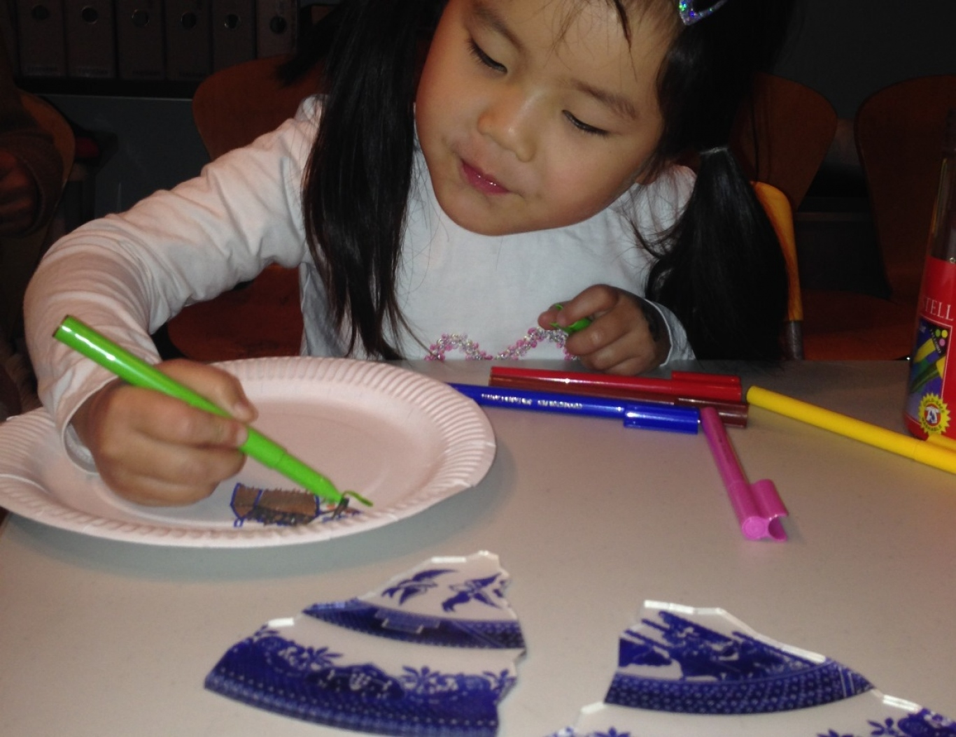 A girl draws her story onto a plate
