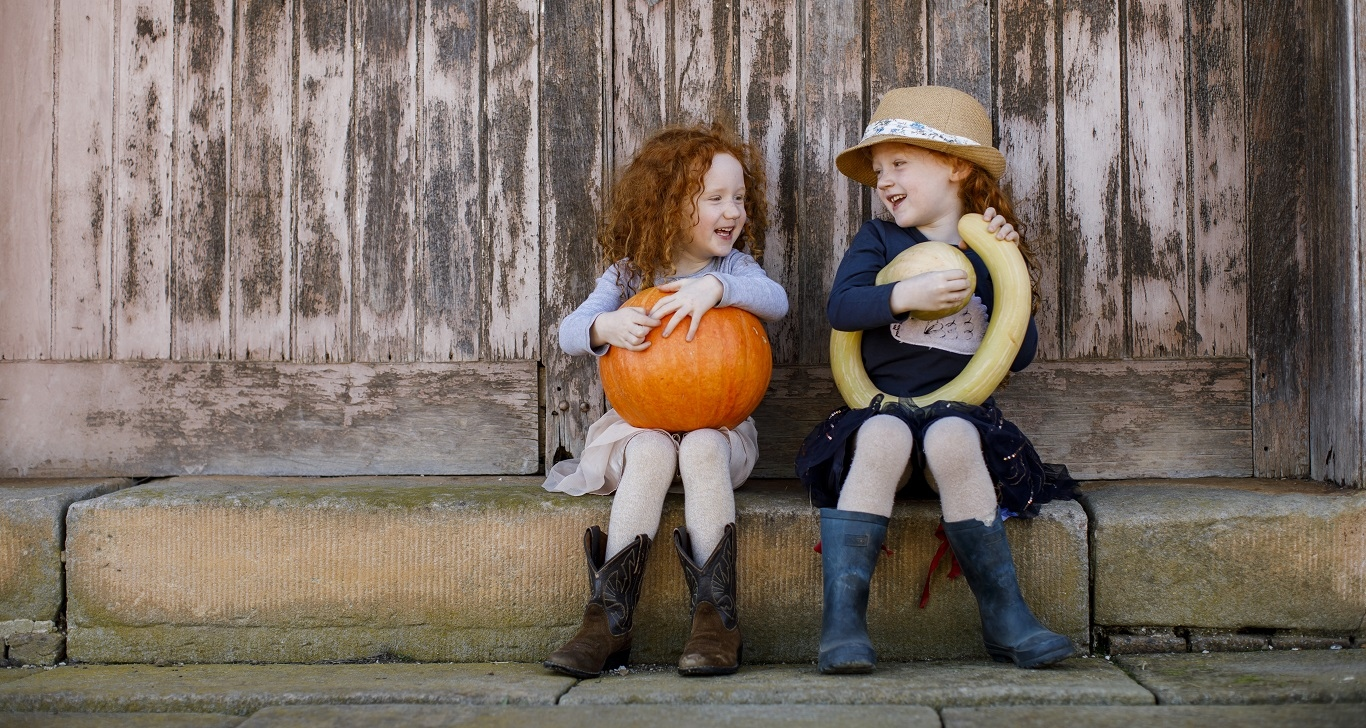 Two children sitting on high pavement, one holding large pumpkin, the other a curly marrow.