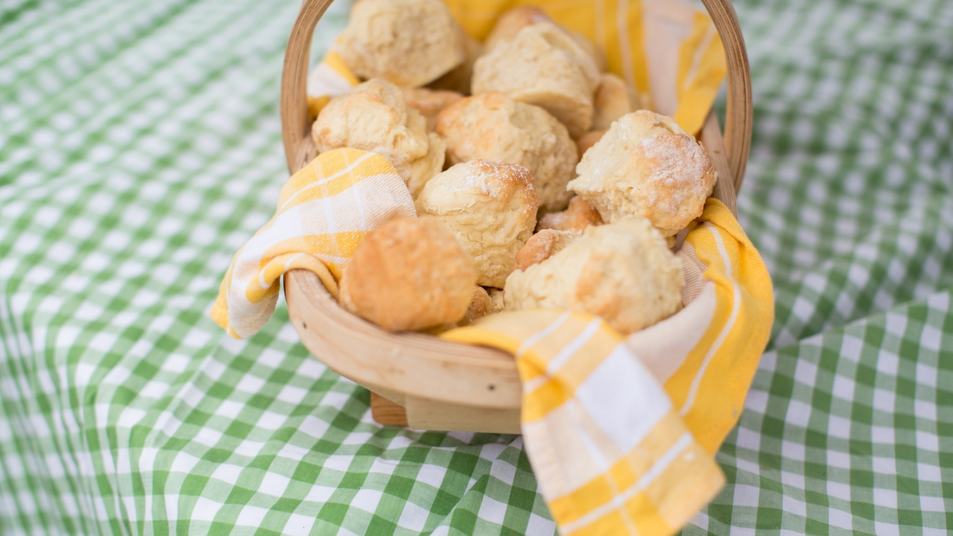 Scones in a yellow cloth-lined basket on a green check tablecloth.