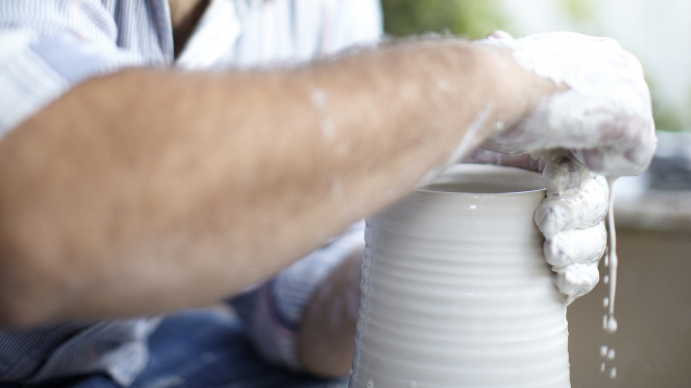 close up view of potter turning a clay vessel with water dripping through fingers