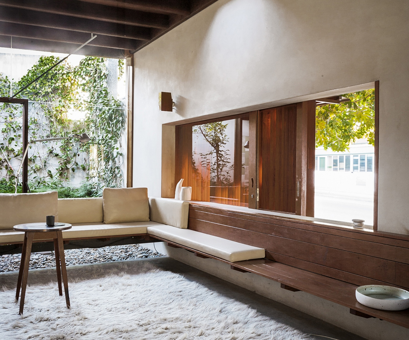 Interior of the D House in  Brisbane's New Farm,showing thick rug, wooden bench seats and big sunlit windows