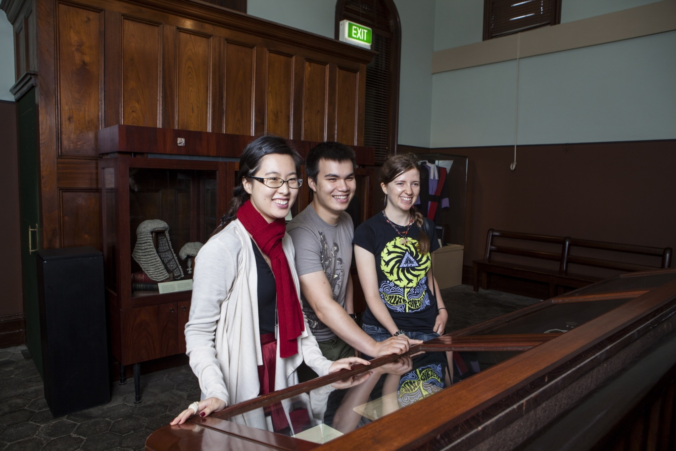 Three young people in courtroom setting.