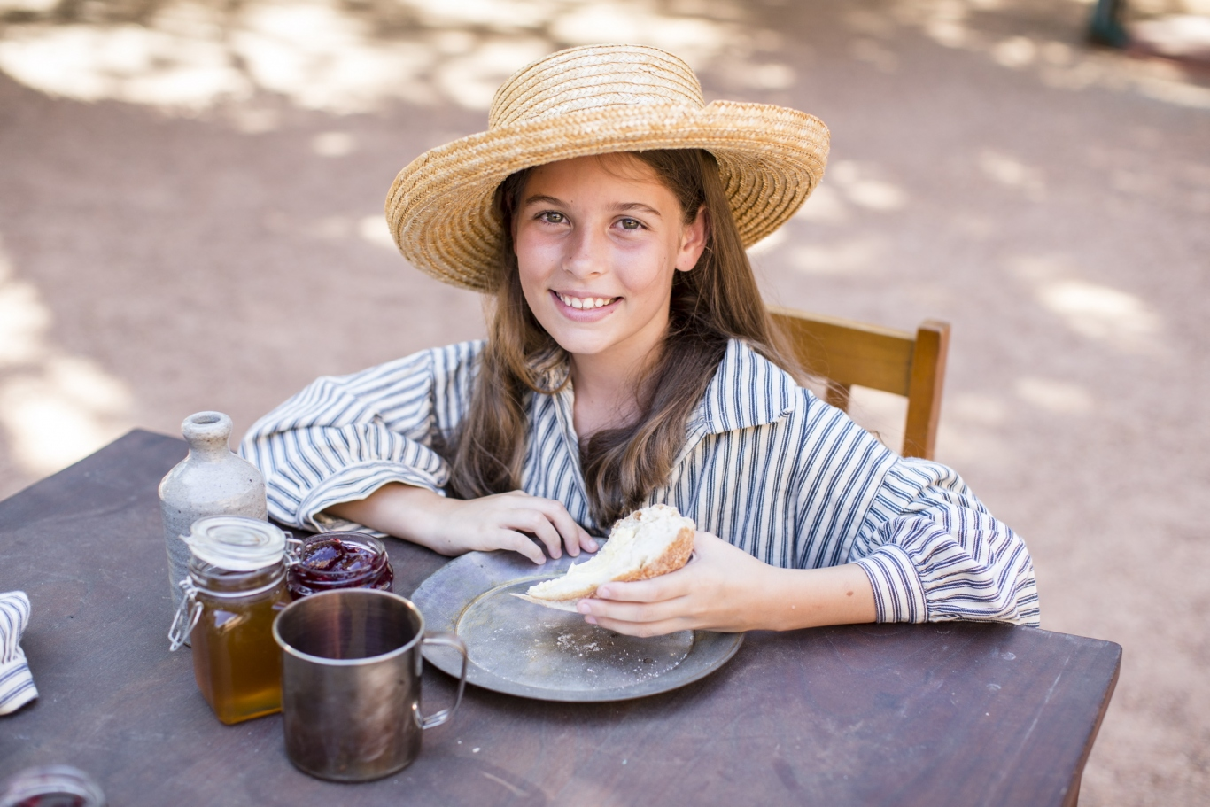 Girl in convict dress sitting at a table