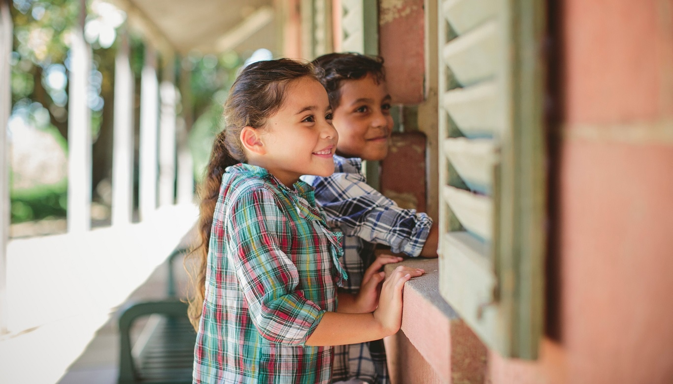 Two children looking in through window from verandah.