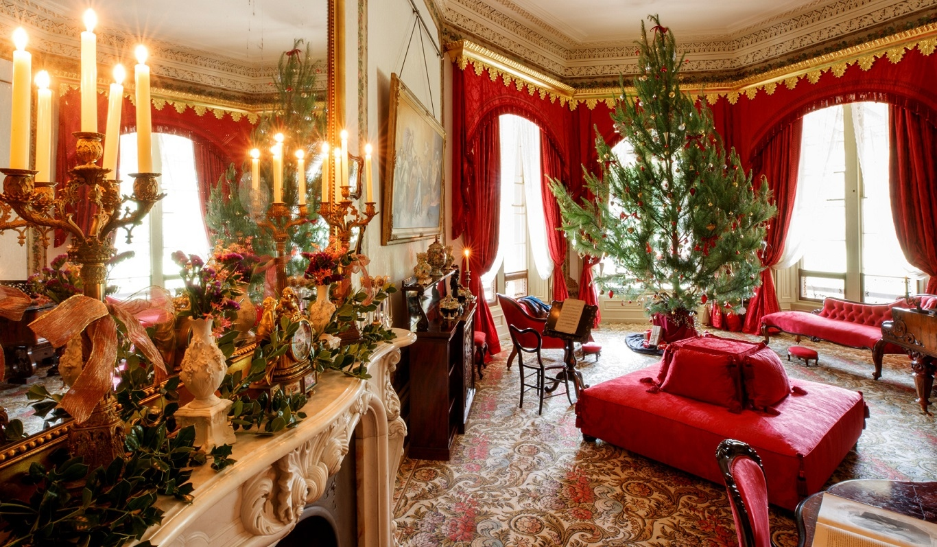 Decorated tree in lavish drawing room with decorated fireplace and period furniture.