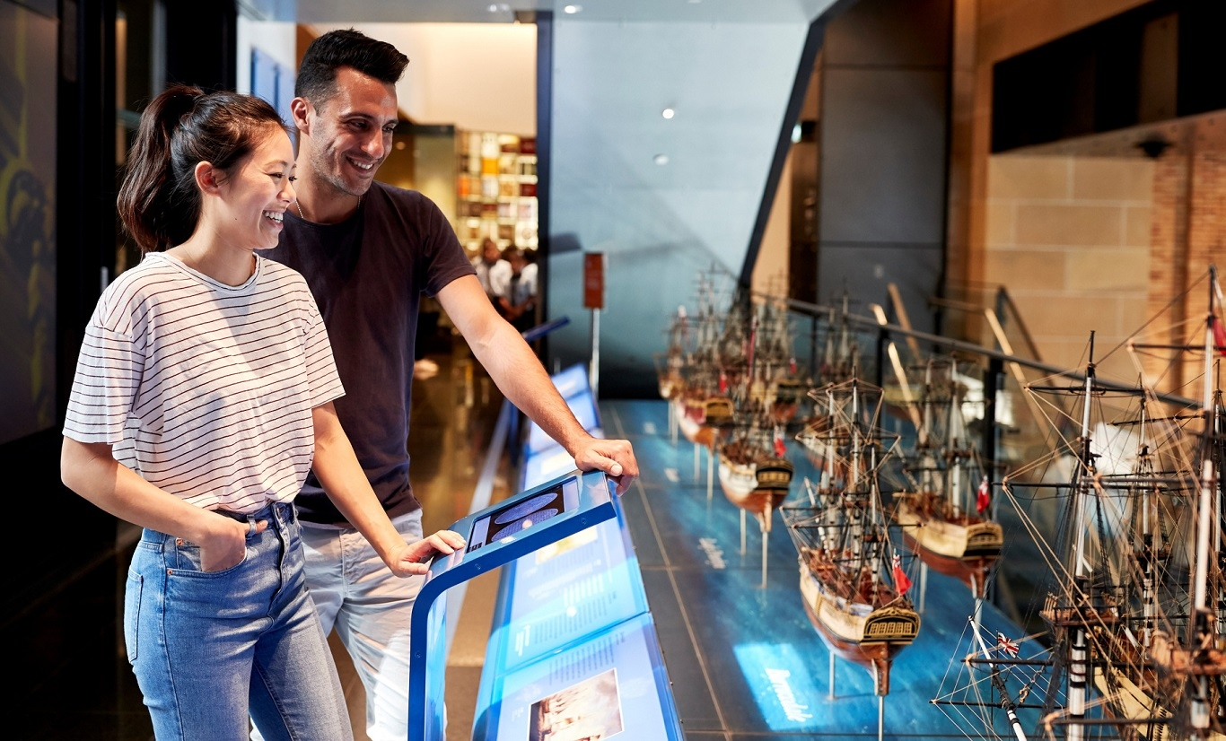 A couple view the First Fleet Ships model display in the Museum of Sydney
