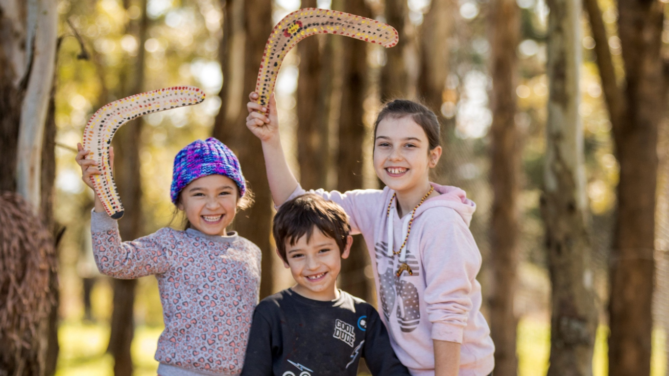 Three children, two with boomerangs held up over head, in outdoor setting with trees behind them.