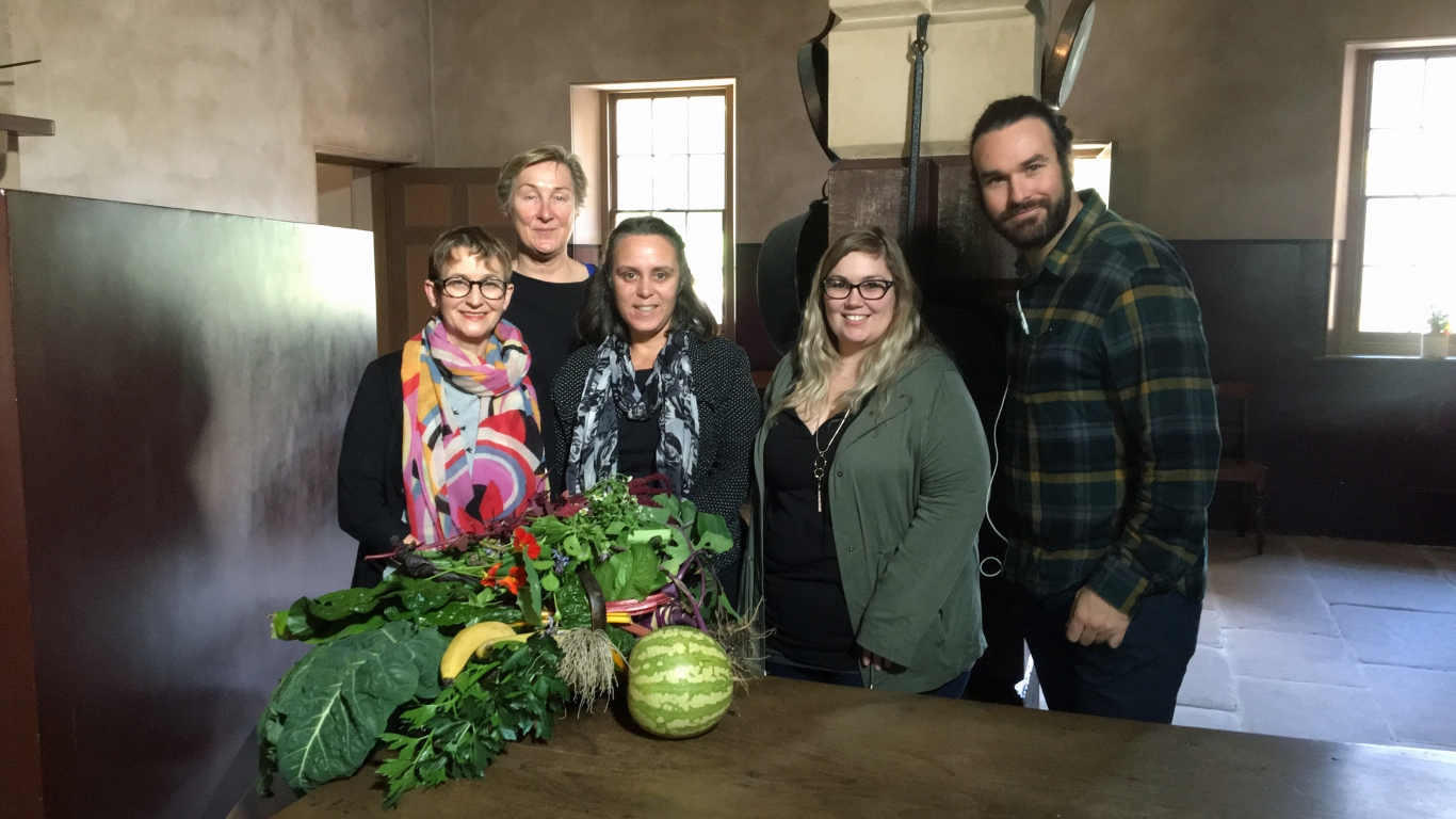 Group in kitchen with fresh produce on table.