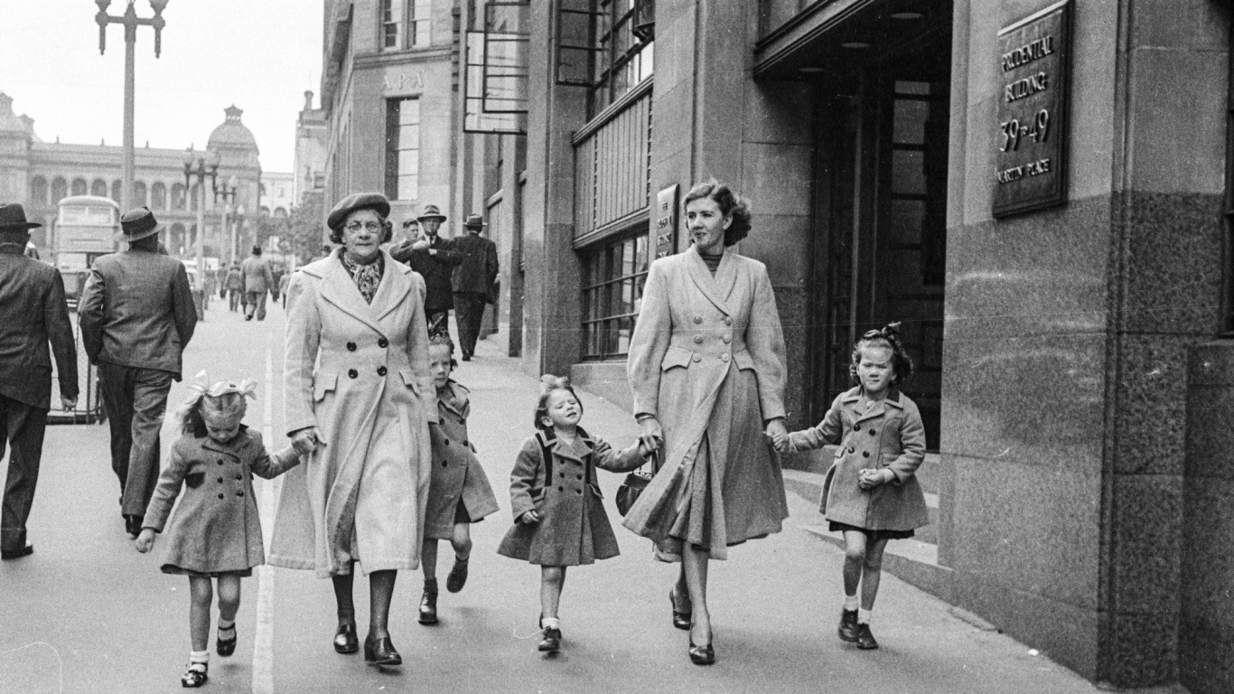 Black and white photograph of two adults and three children walking in a line holding hands in urban setting. This view is up Martin Place toward Macquarie Street, Sydney.