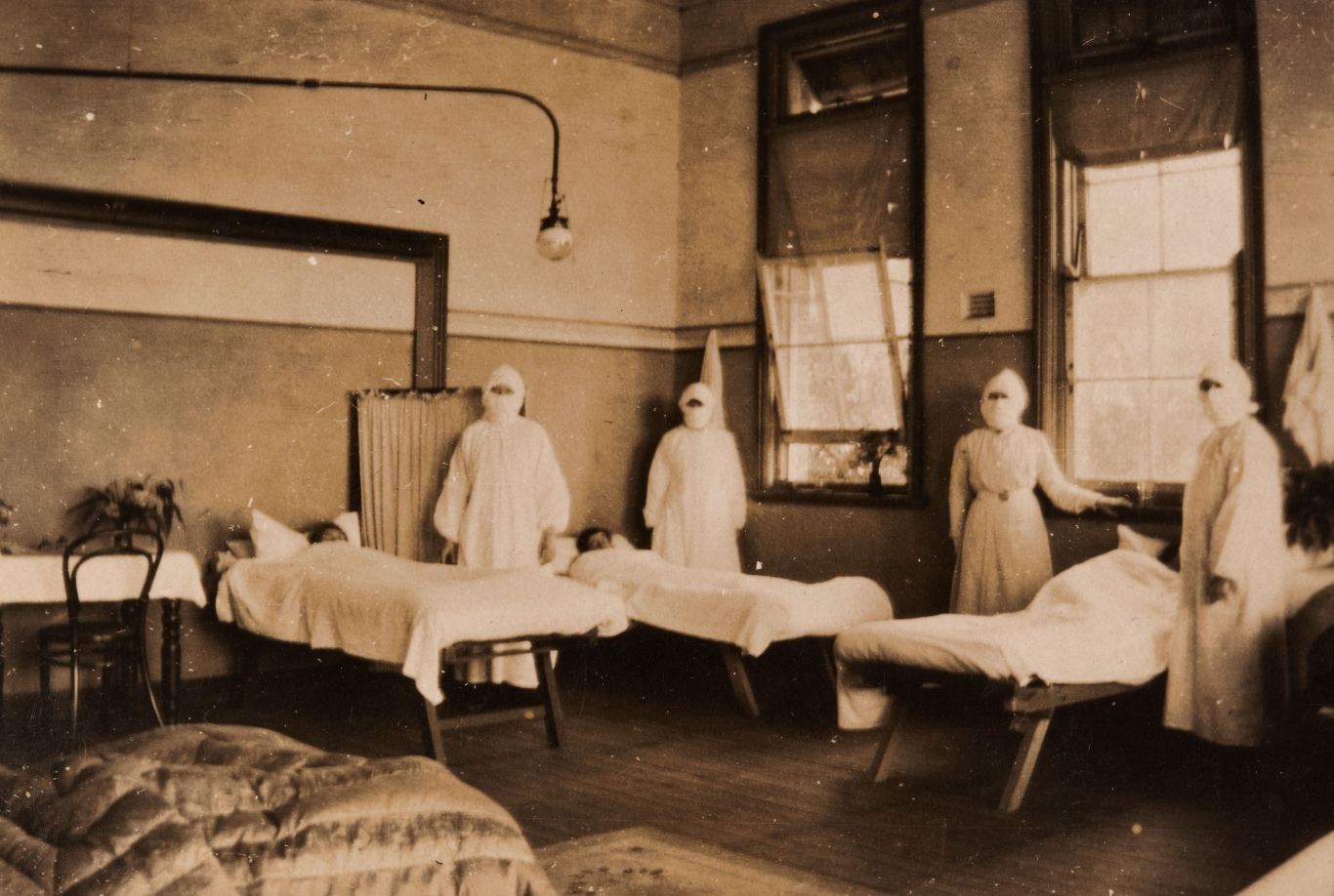 Photograph of four nurses in a school converted into a hospital ward, 1919.