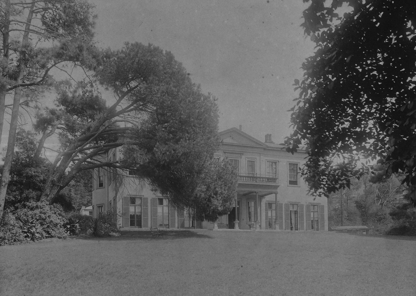 B/w photo of a large 2 storey house seen through the trees across a wide lawn.