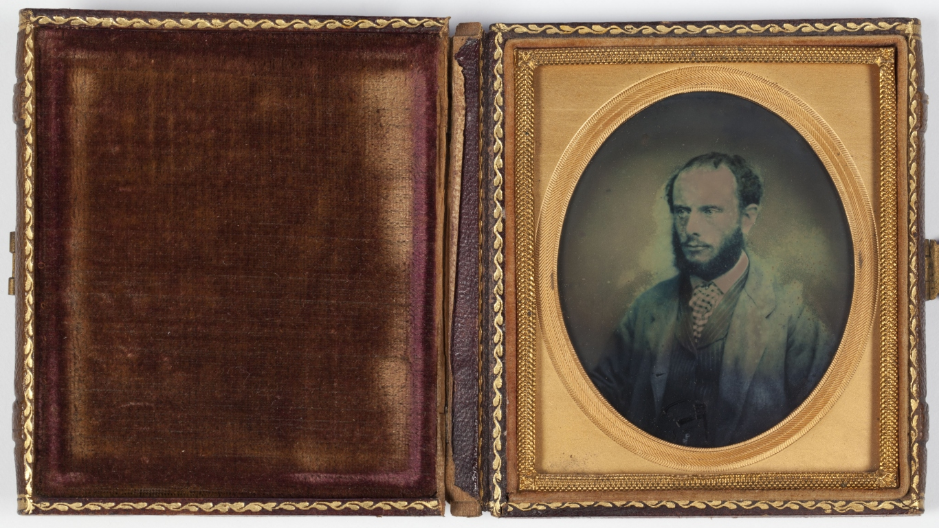 Green tinged portrait of man with short bushy beard, wearing jacked, vest, shirt and scarf. The photo is housed in a cameo frame mount within a folding leather case with gold plush trim and gilt metal clasp.