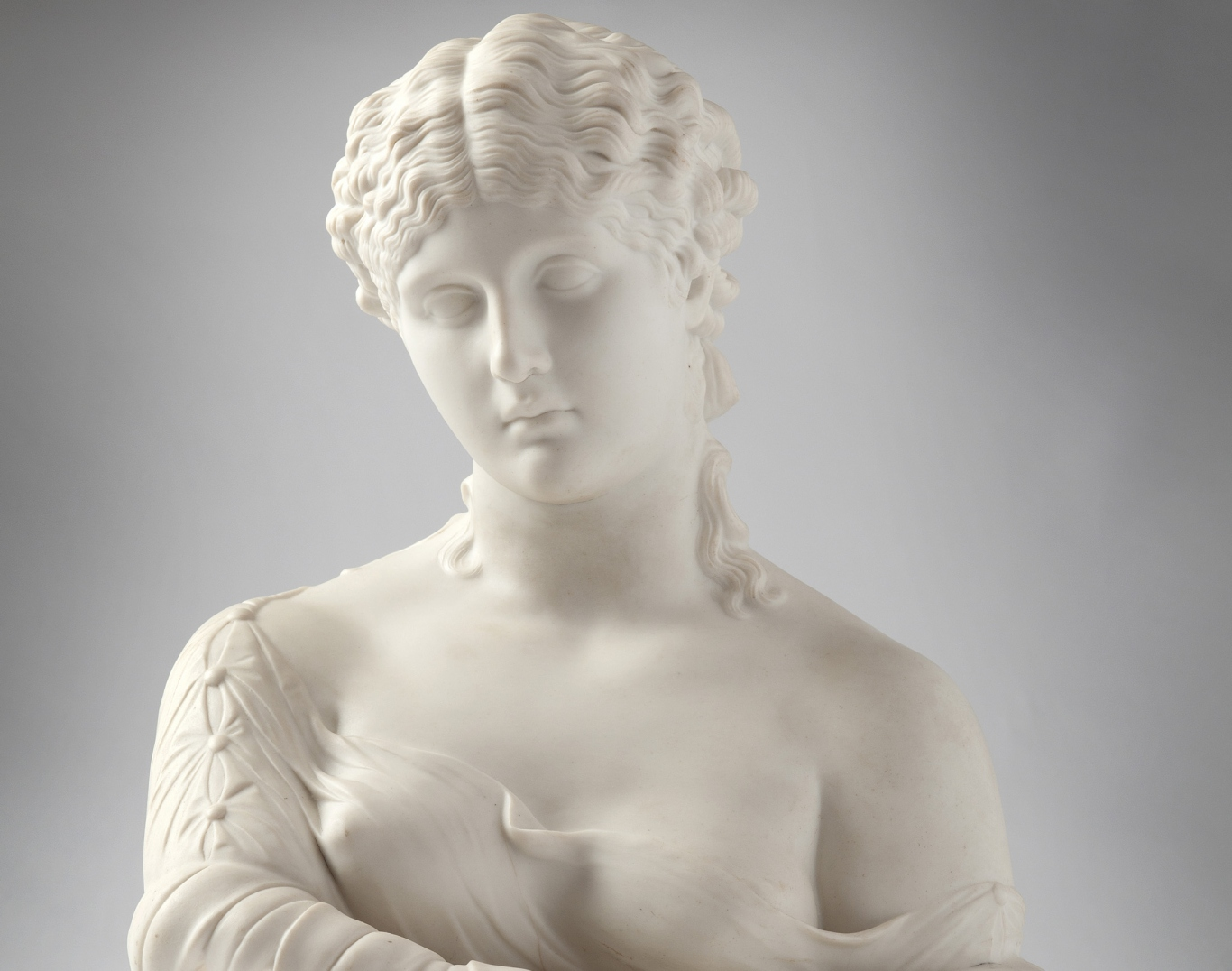 Head and shoulders of white bust of young woman.