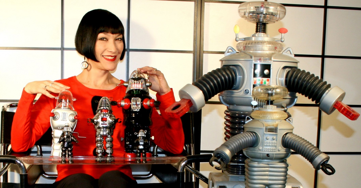 claudia Chan Shaw poses with a small collection of robots