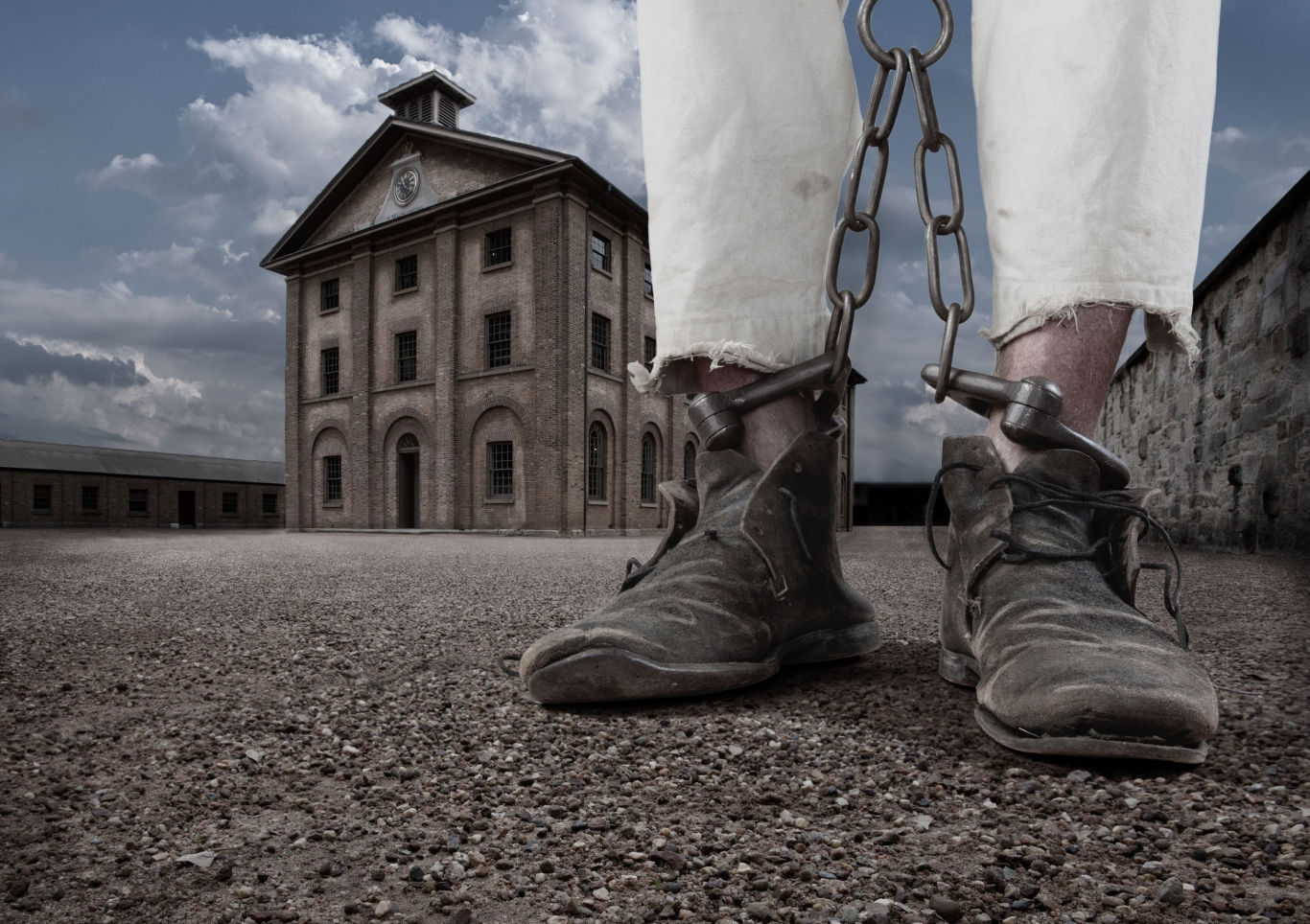 Image of chained legs (boots and white trousers visible) with Hyde Park Barracks in background.