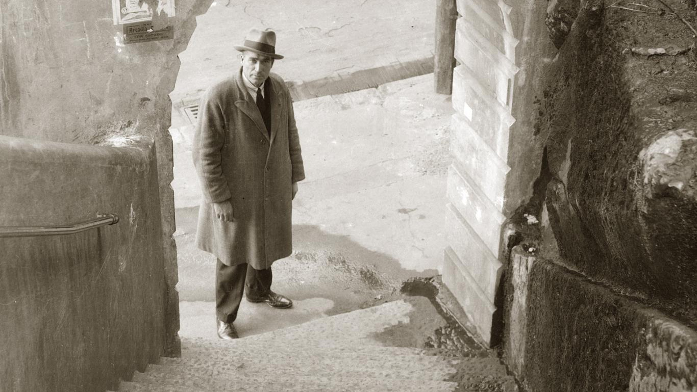 Cropped black and white photo of man wearing hat and long coat looking up stairs.