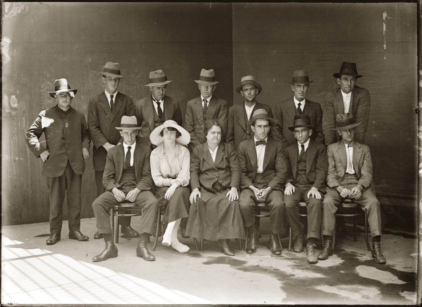 Black and white photo - group mugshot of men and women seated and standing.