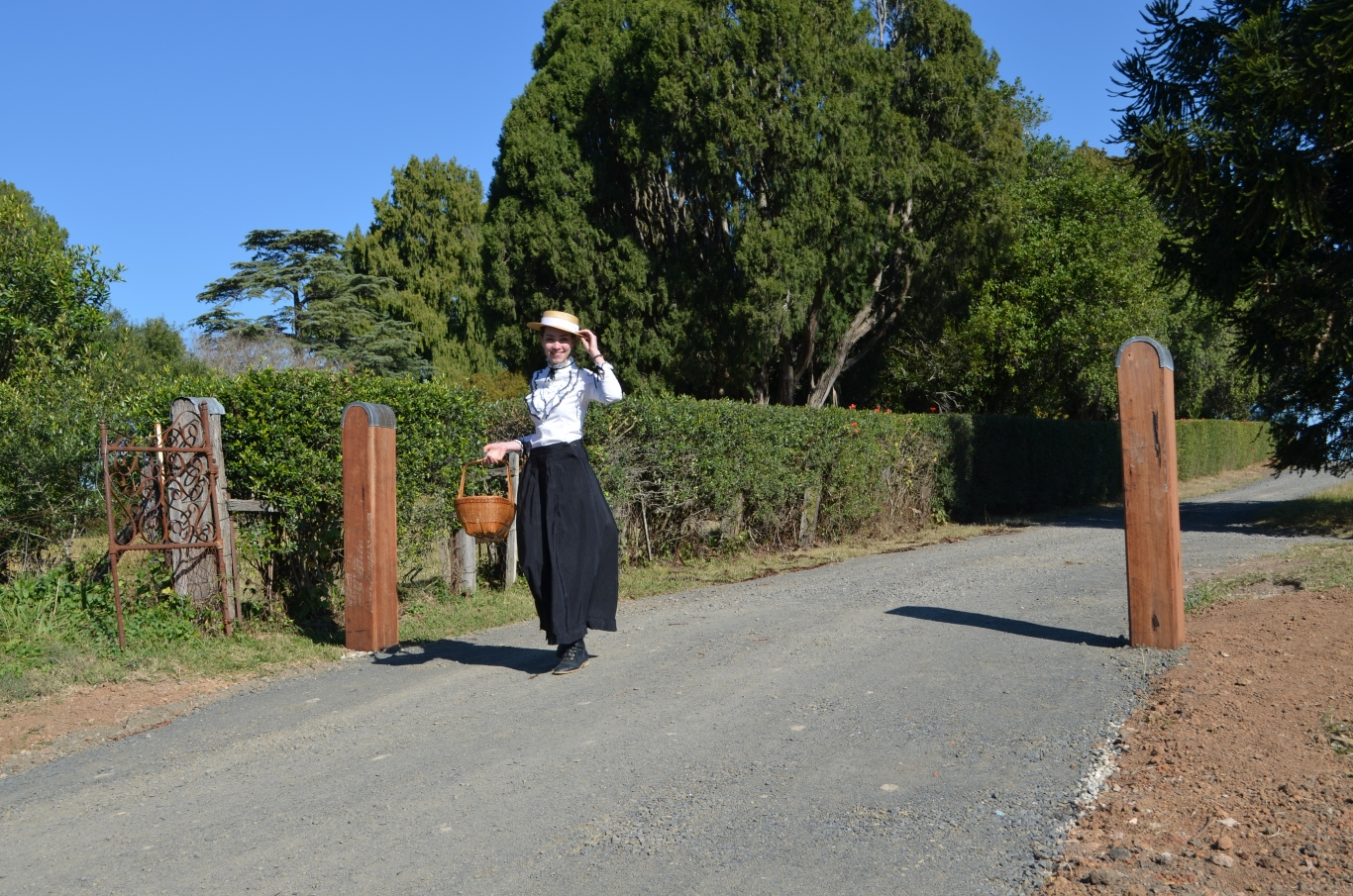 Young woman dressed in period costume with straw hat walking down gravel driveway between gateposts.