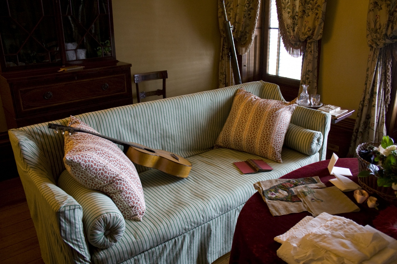 Richly furnished room featuring a striped green sofa with pillows, bolsters, a book and a guitar on it, surrounding by furniture displaying scattered ornaments, pieces of fabric, books and letters underway. In the background are french doors and curtains.