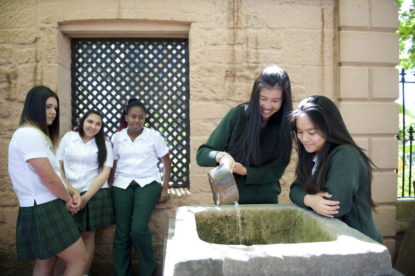 Students scooping water from the dripstone in the courtyard at Elizabeth Farm.