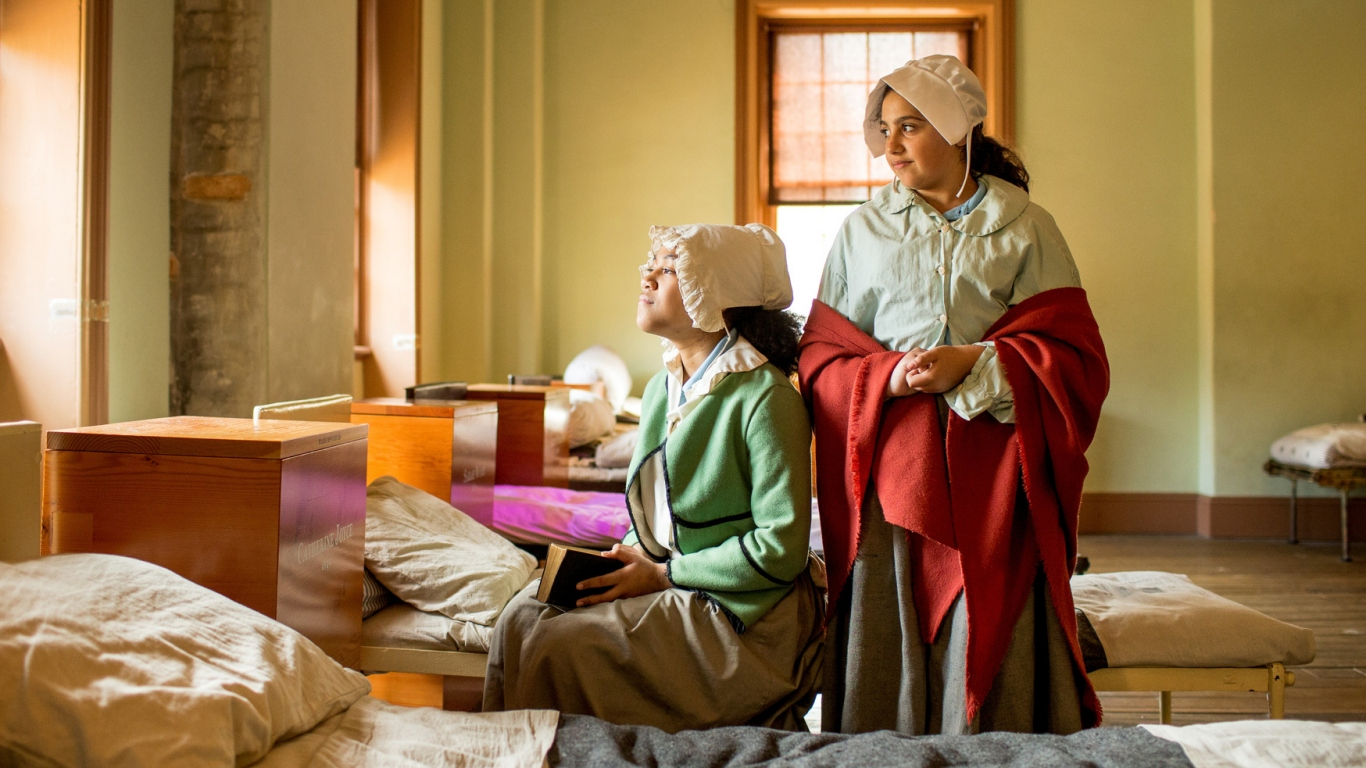Two girls dressed in costume in large dormitory style room.