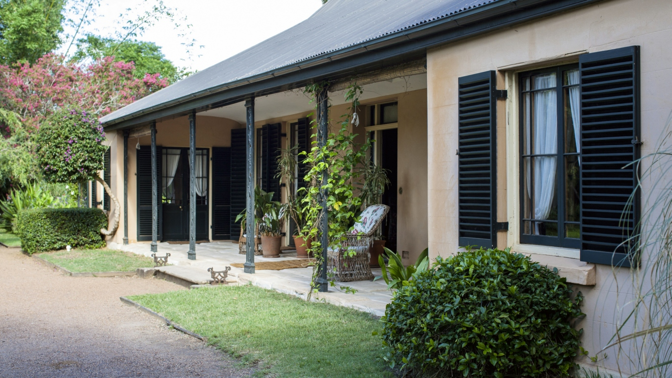 Colonial era farmhouse with armchairs on flagged verandah.