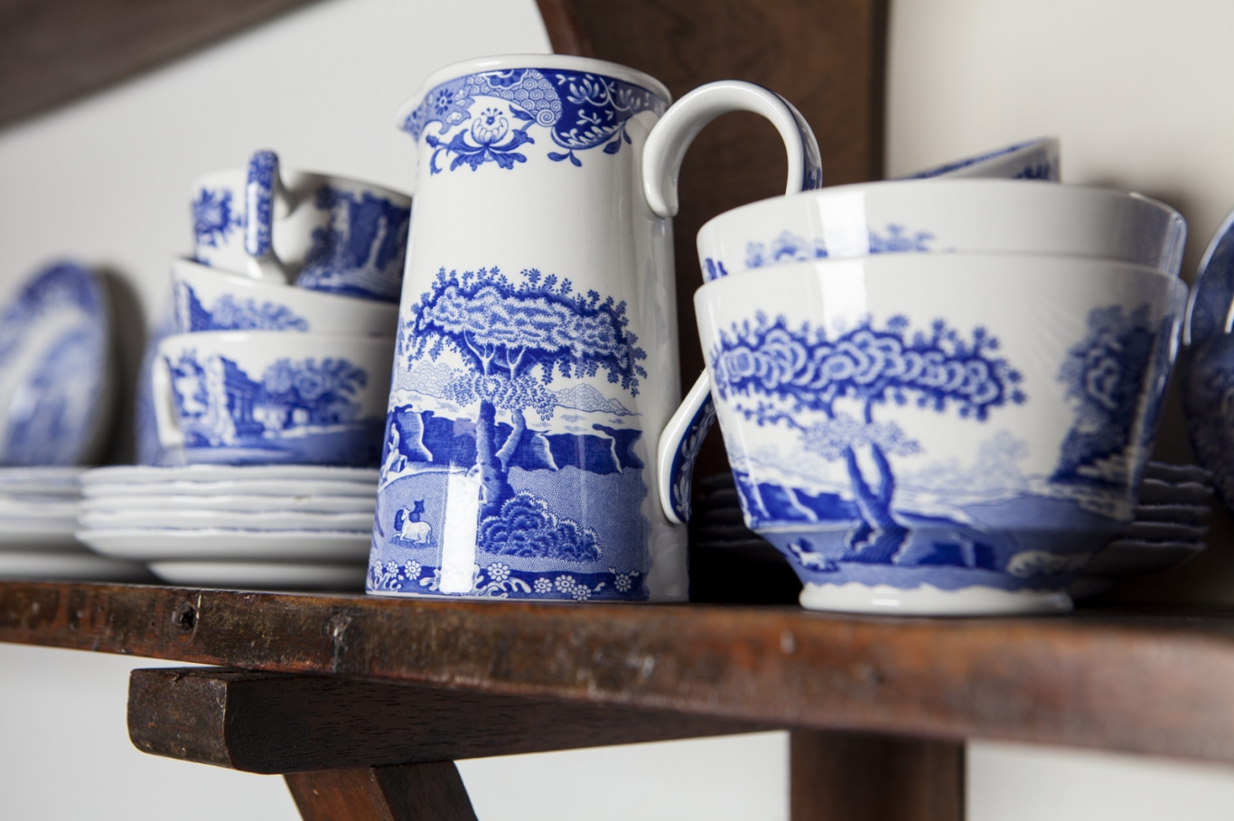 Row of blue and white crockery items on a wooden shelf.