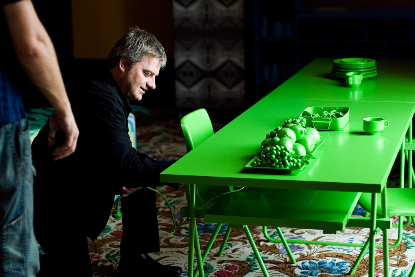 Image of a man making adjustments to a green table