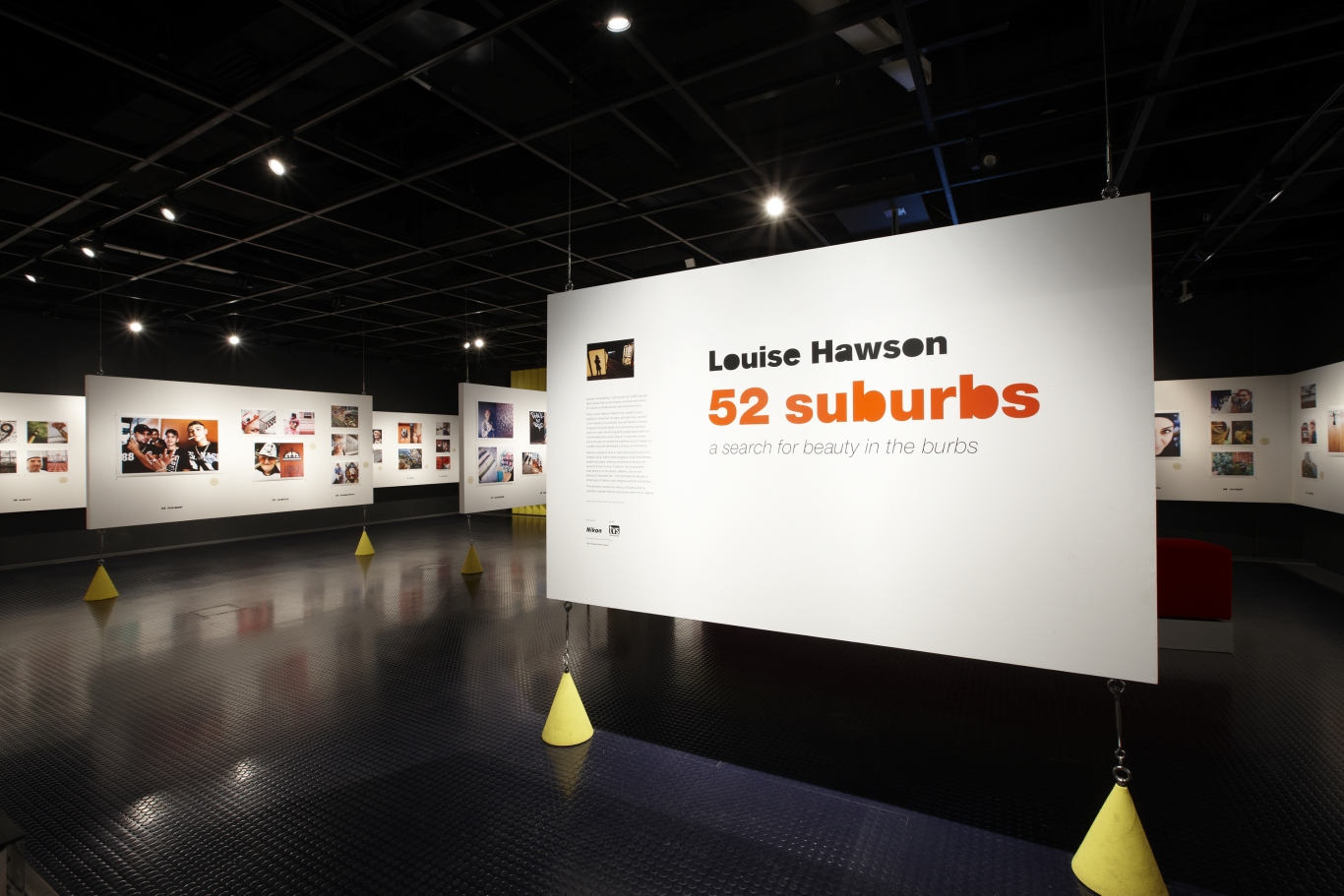 Photo of the 52 Suburbs exhibition. A large panel isin the foreground with the exhibition titlle printed on it.