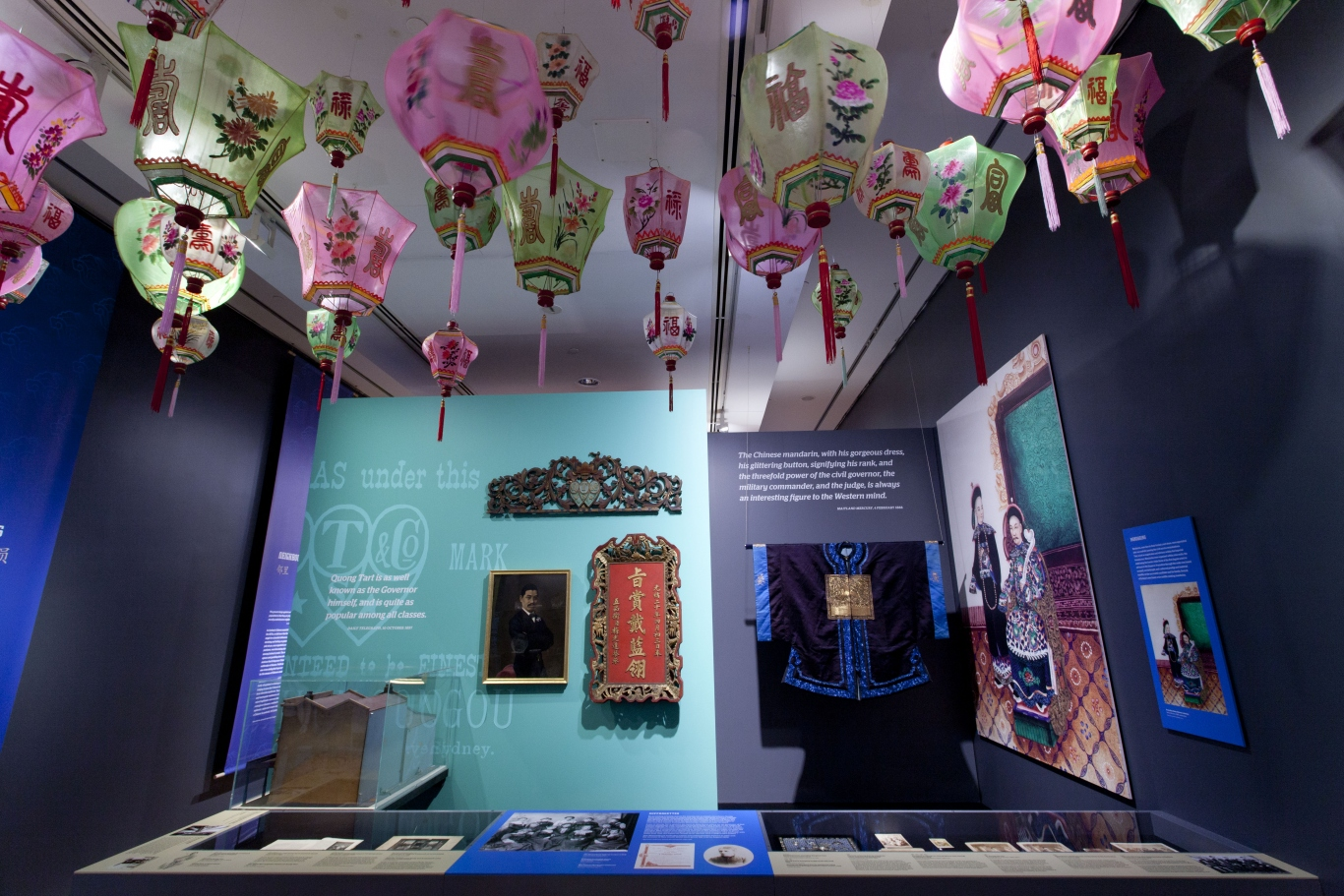 Exhibition view featuring objects in showcases and colourful Shanghai lanterns overhead