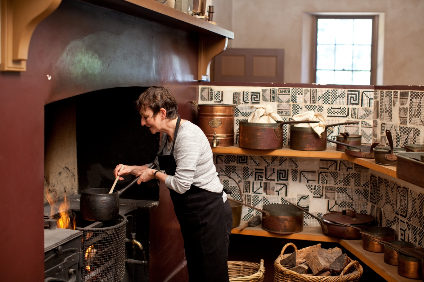 Kitchen interior with woman cooking over flame.