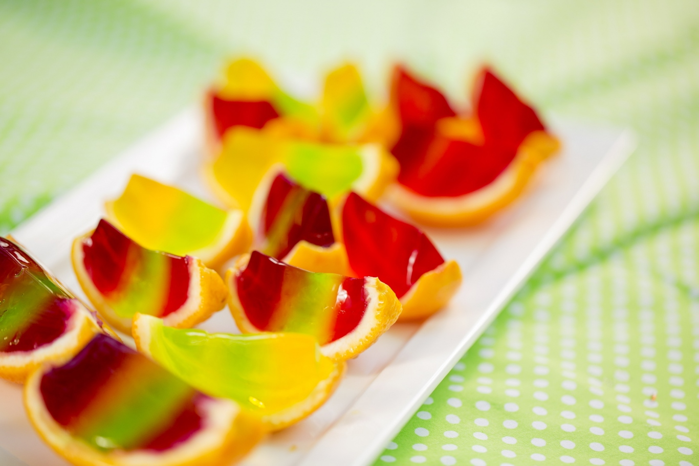 Colourful selection of jellied orange segments on table.