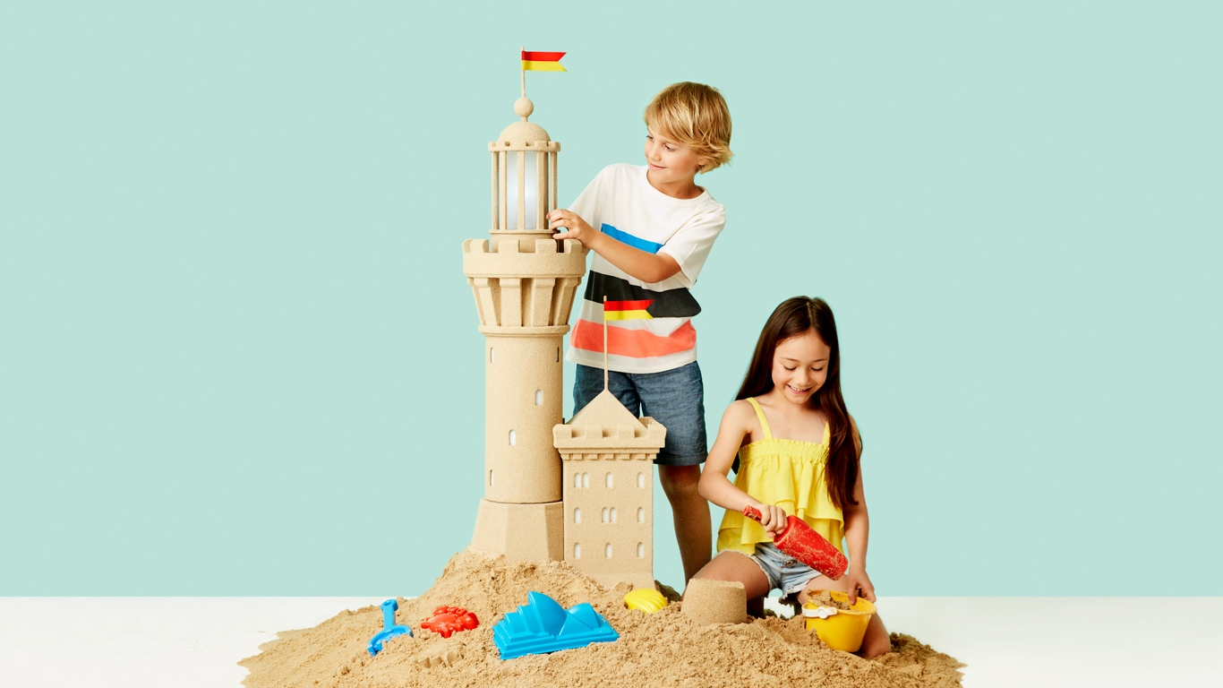 A young boy and girl play with a sand castle tower