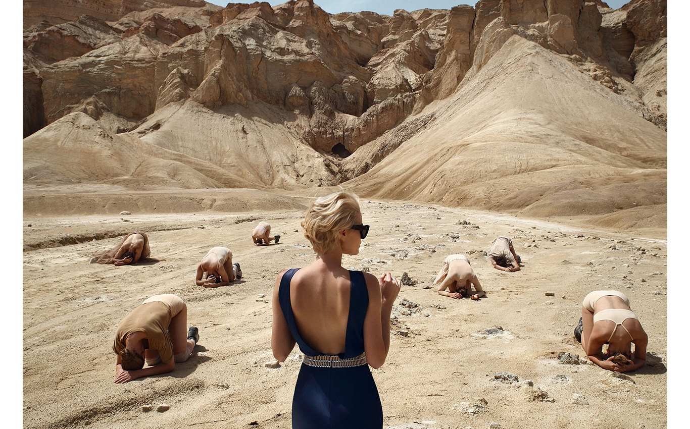 Woman in mountainous desert setting with group of people curled over on ground in artistic arrangement.