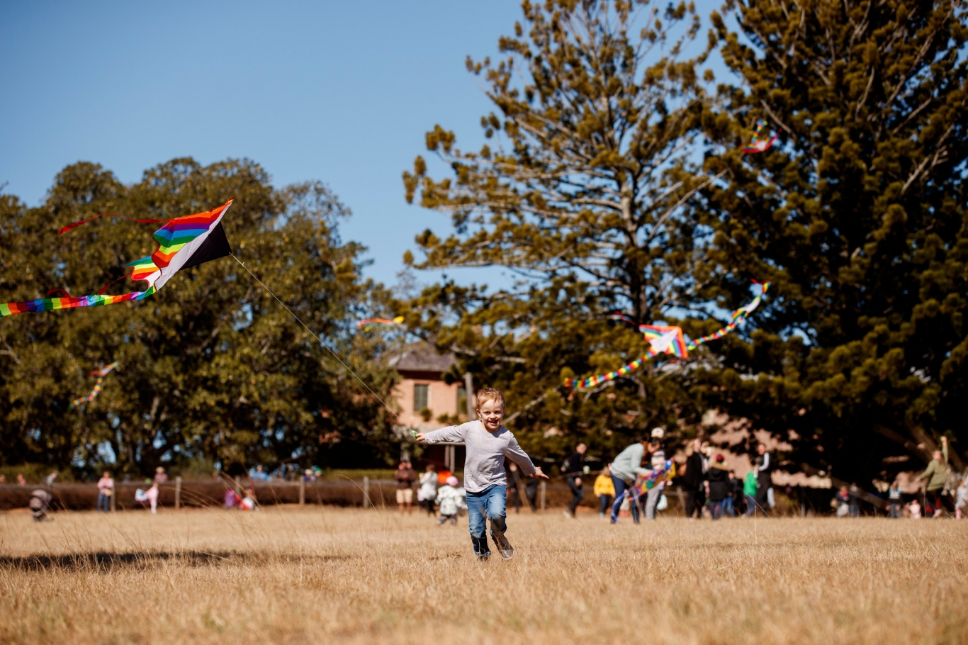 Child running with flying kite in paddock, with trees and buildings behind.
