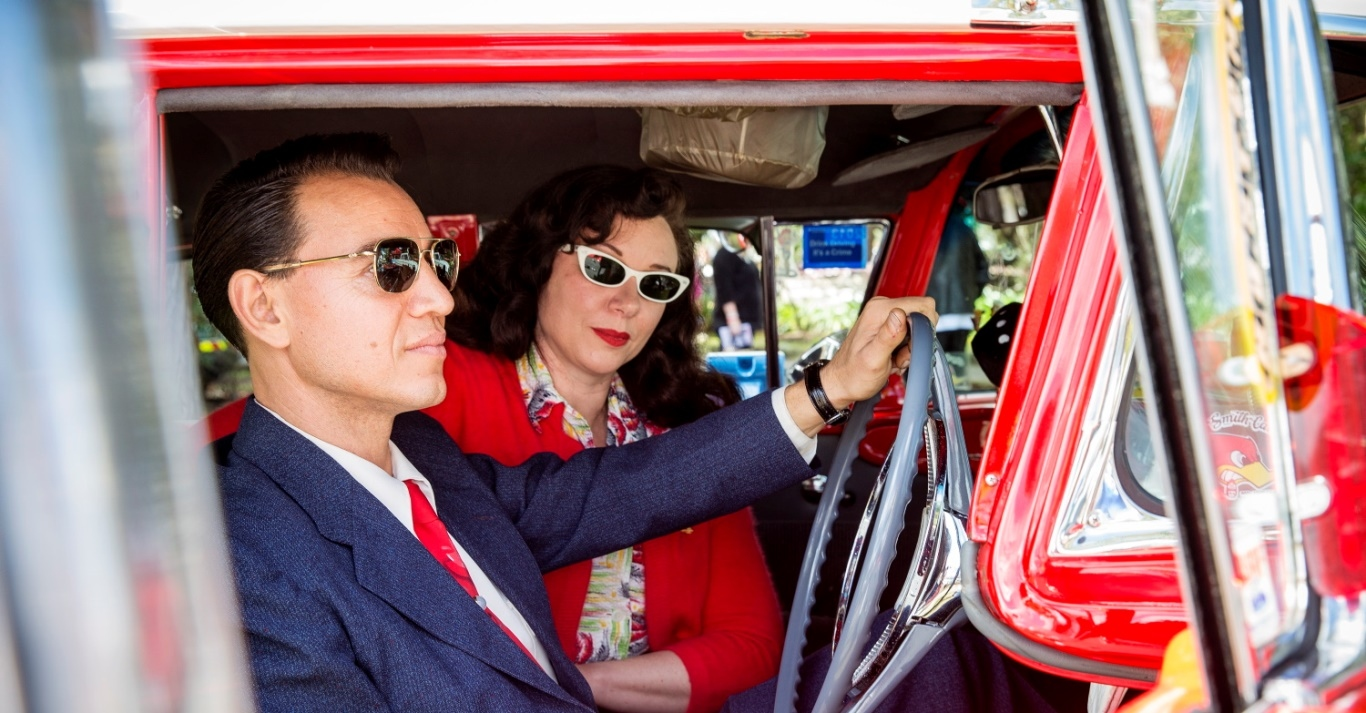 Man and woman in Fifties attire sit in a red car