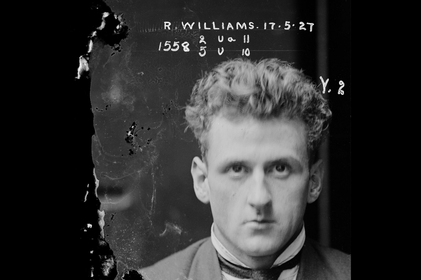 Black and white photo of man's face with white writing on negative visible to one side.