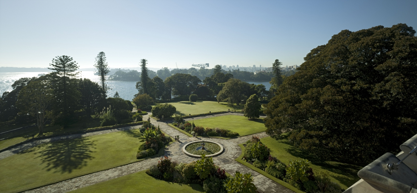 View from turrets of government house over the eastern garden showing sandstone paved paths, fountain, lawns and a spectacular view of sydney harbour in the distance