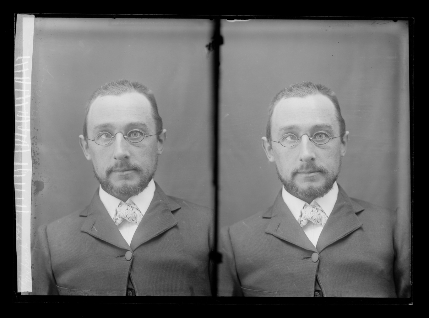 Double glass plate black and white photo of man with short beard, wire-framed glasses and a slightly turned in eye.