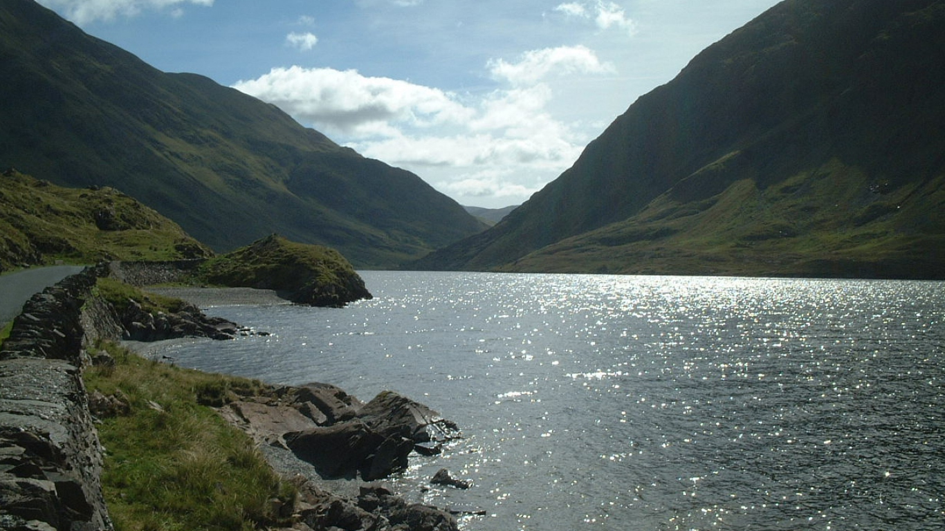 Dramatic photo of lake or river with rocky shore, bordered with high grassy mountains and a road along the left hand shore.