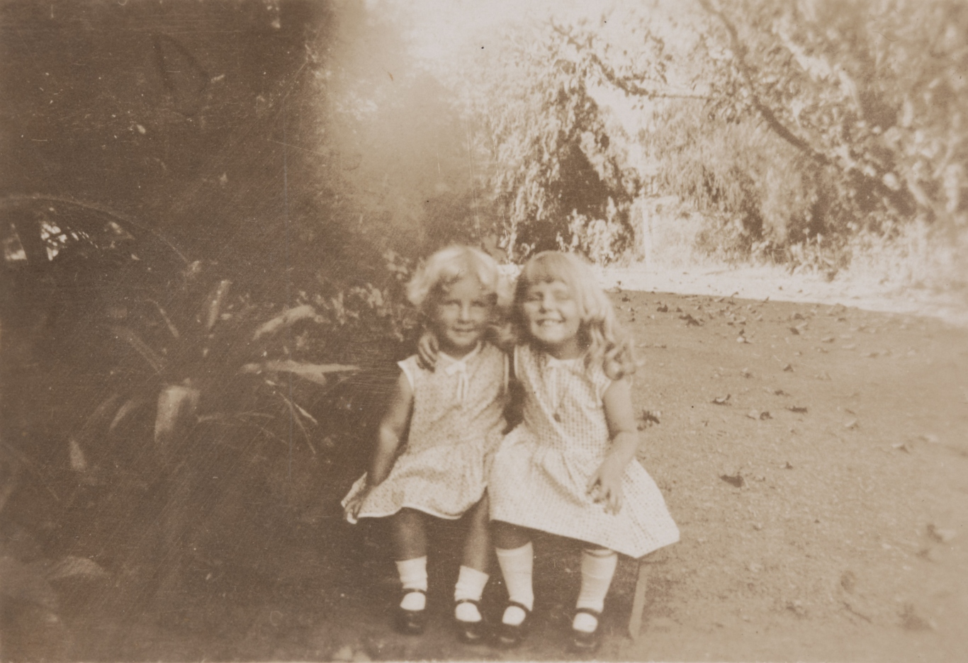 Sepia toned photo of two young girls in light dresses, socks and mary jane style shoes seated on step with their arms around each others' shoulders.