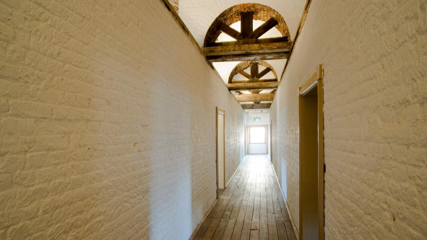 Long corridor with wooden floor, painted brick walls and wooden arches above, leading to backlit window at far end.