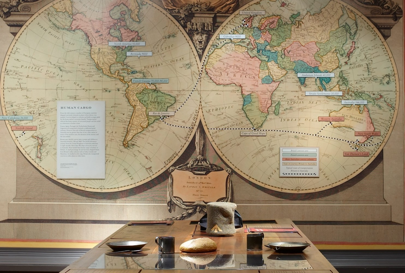 View of Convict Sydney exhibition showing table with artifacts and wall maps