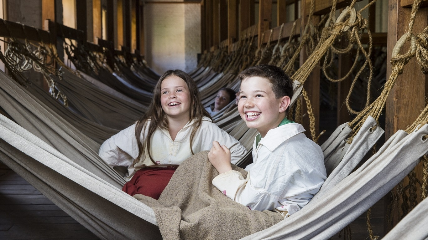 Children dressed as convicts in room full of hammocks tied to timber beams.