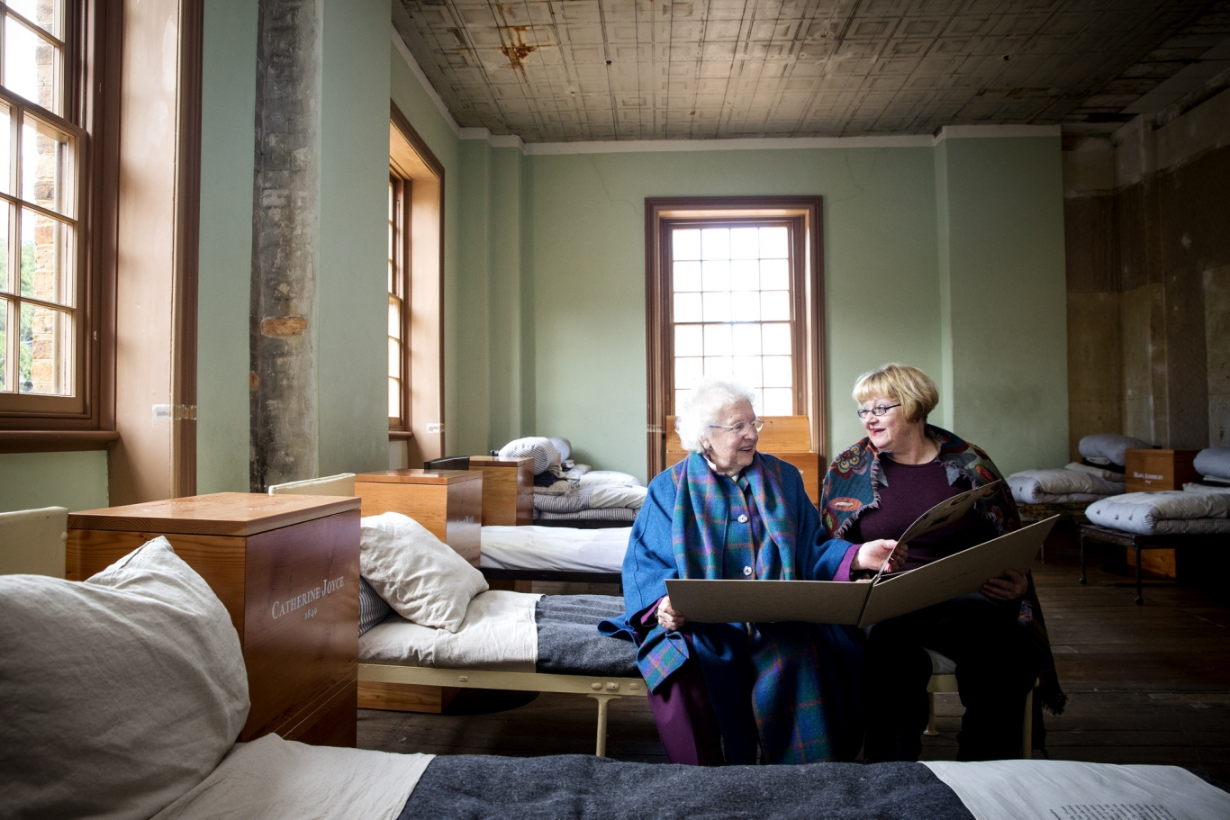 Two women seated on simple bed in dormitory style display holding large book.